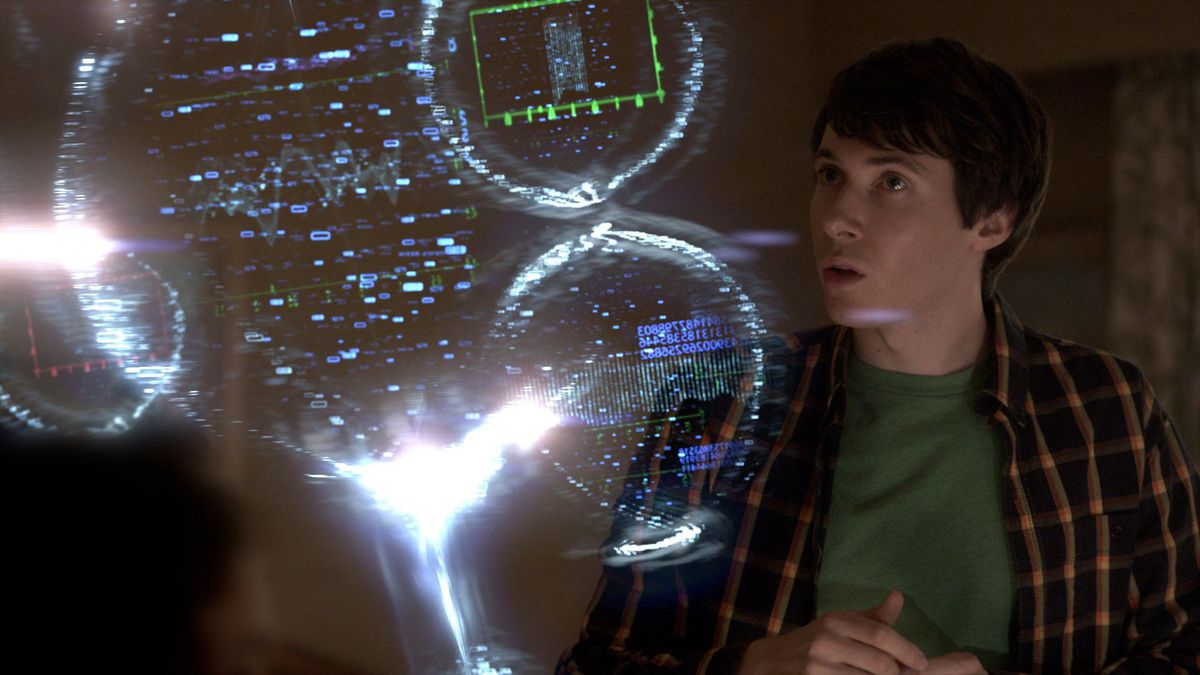 A boy man looks at a projected image of a computer