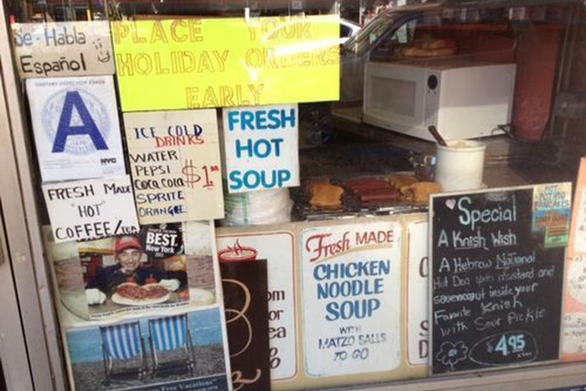 A window at a deli with signs for soup.