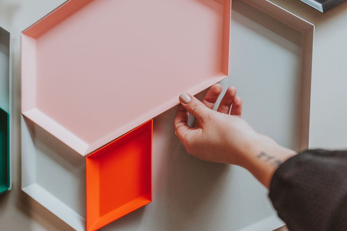 An image of geometric trays in sage, pink, and orange with a woman's hand reaching for the edge.