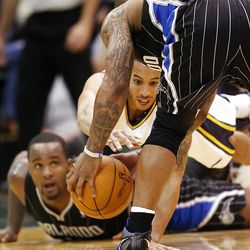 Utah Jazz guard Devin Harris (5), center, tries to get a lose ball as he dives over #11 Glen Davis as the Utah Jazz and the Orlando Magic play Saturday, April 21, 2012 in Energy Solutions arena.