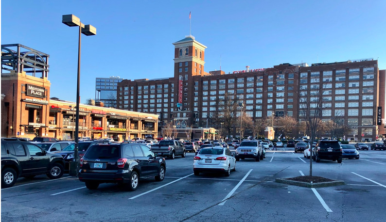 A huge brick building lording over a parking lot.