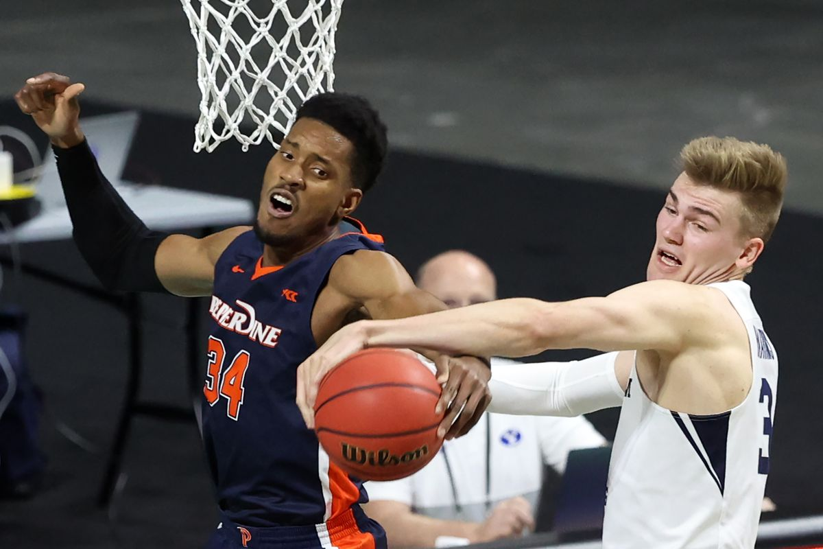 Pepperdine Waves center Victor Ohia Obioha (34) and Brigham Young Cougars forward Matt Haarms (3) work for a rebound as BYU and Pepperdine play in semifinal West Coast Conference tournament basketball action at the Orleans Arena in Las Vegas on Monday, March 8, 2021.