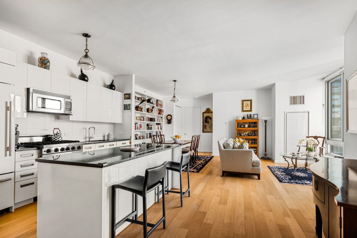A kitchen with white cabinetry, an island with two chairs, and hardwood floors.