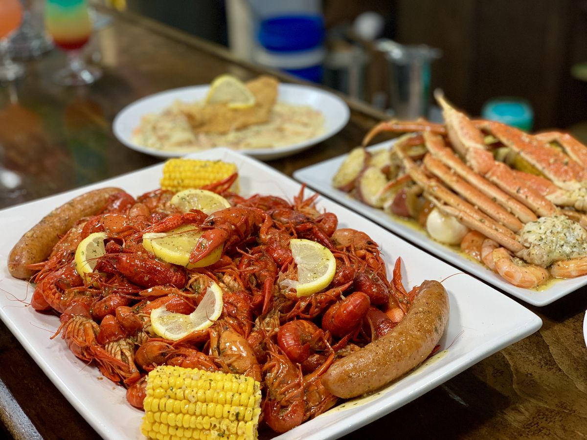 A platter of boiled crawfish with potatoes, and corn and a plate of snow crab legs