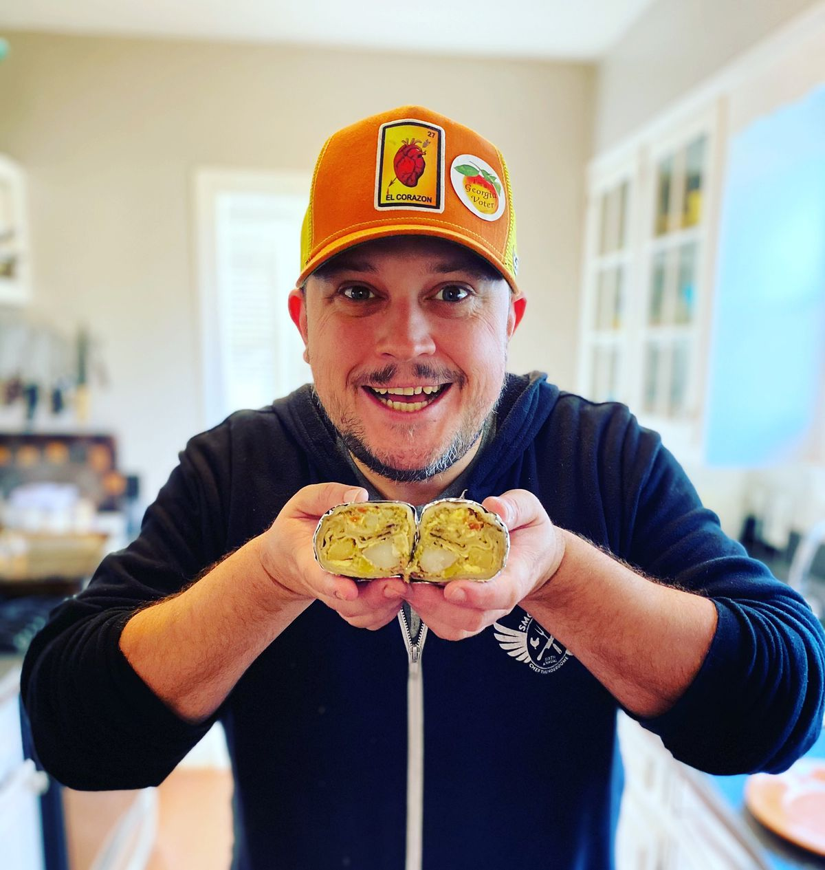 Chef Nick Melvin smiling in a navy blue hoodie and orange trucker ball cap holding an egg, potato, and cheese burrito cut in half in two hands