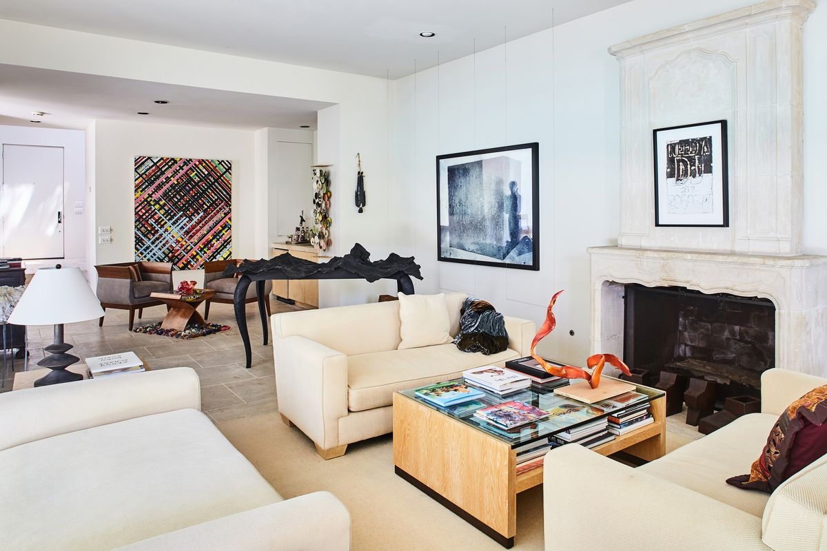 Eclectic living room image, white walls, cream colored pretty marble fireplace. Cream colored chairs and couch, natural wood coffee table with lots of books covering it. A black table sculpture and colorful painting in the background.