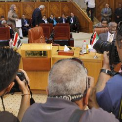 Cameramen document the Syrian delegation's empty chairs during the Arab League's ministerial council meeting at the Arab League headquarters in Cairo, Egypt, Wednesday, Sept. 5, 2012. Egyptian President Mohammed Morsi said during the meeting that Syrian leader Bashar Assad must learn from 'recent history' and step down before it is too late.