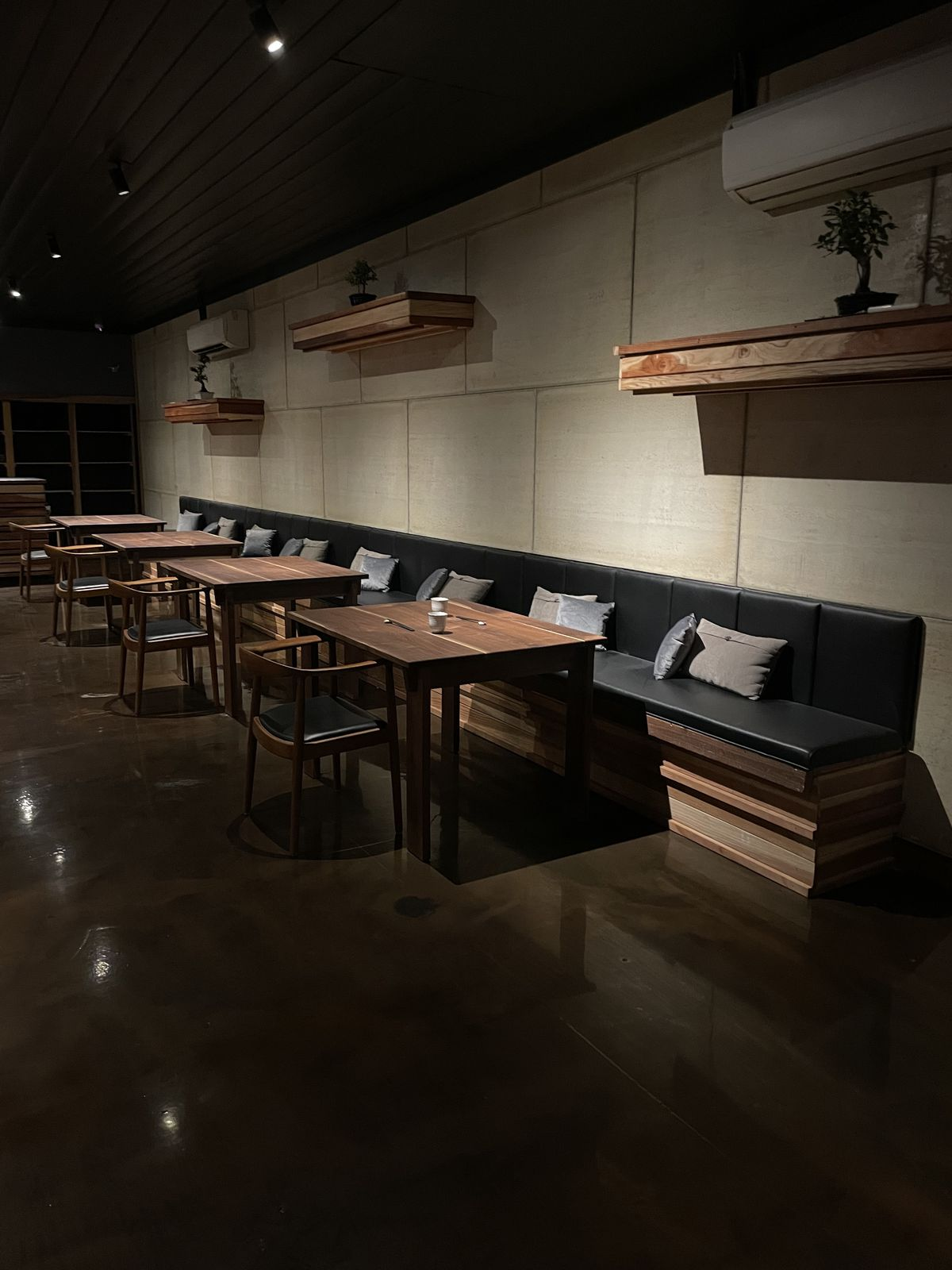 A banquette along the wall with four tables and chairs. On the wall are three shelves with bonsai trees.