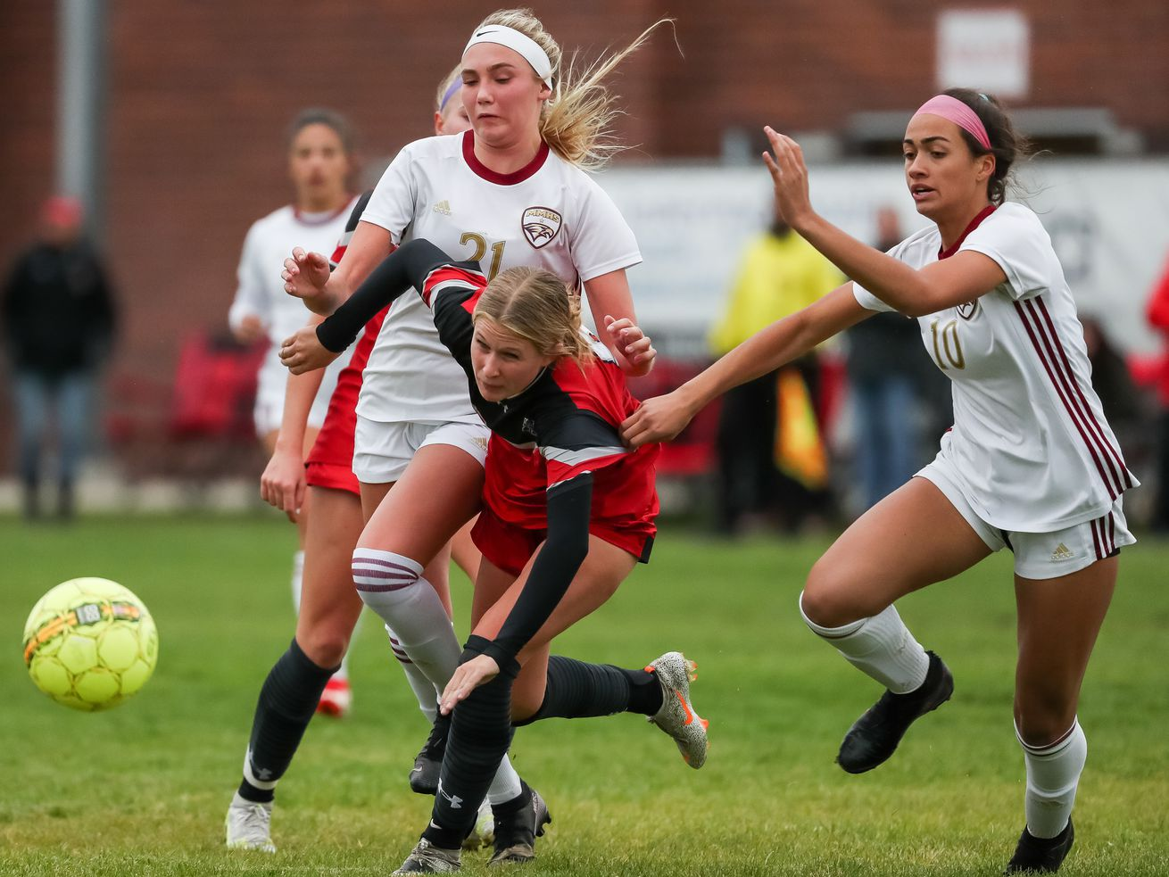 Alta's Isabella Woods stumbles as she rushes between Maple Mountain's Eislee Carlson, left, and Kesley Jewkes.