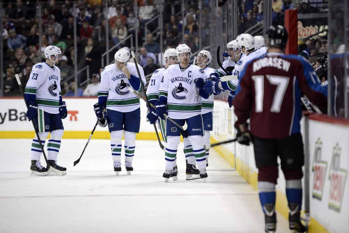 March 24 2012; Denver, CO, USA; Vancouver Canucks center Henrik Sedin (33) is congratulated for his goal during the second period of the game against the Colorado Avalanche at the Pepsi Center. Mandatory Credit: Ron Chenoy-US PRESSWIRE