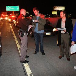 Trooper Wyatt Weber of the Utah Highway Patrol talks with drivers at the scene of a non-injury accident on I-15, Thursday, Dec. 13, 2012.
