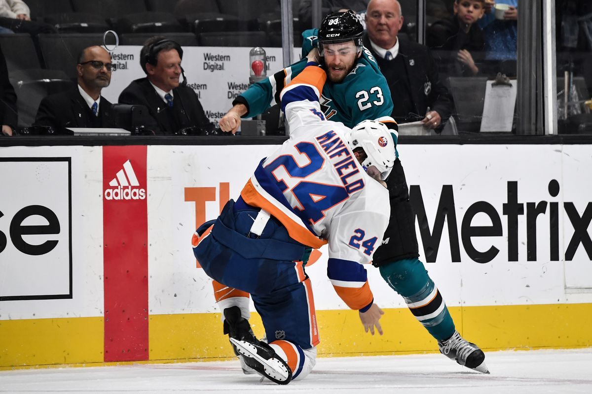 Barclay Goodrow #23 of the San Jose Sharks throws fists with Scott Mayfield #24 of the New York Islanders at SAP Center on October 20, 2018 in San Jose, California