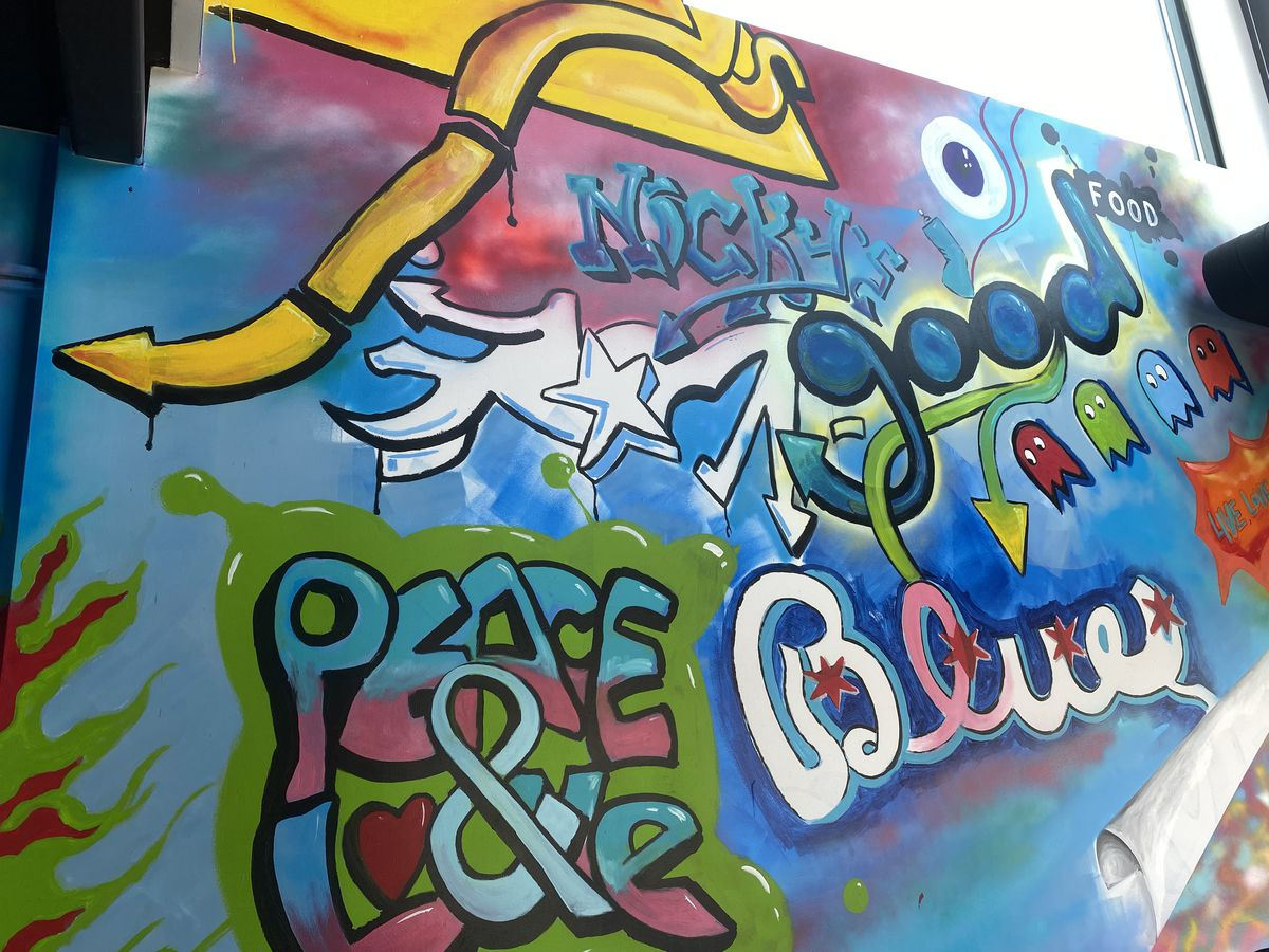 Inside Nicky's of Beverly, the walls of the fast food restaurant feature street art and hippie flair.