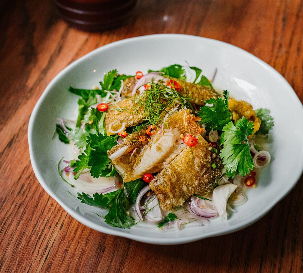 Plate of crispy seafood in white bowl on wooden table