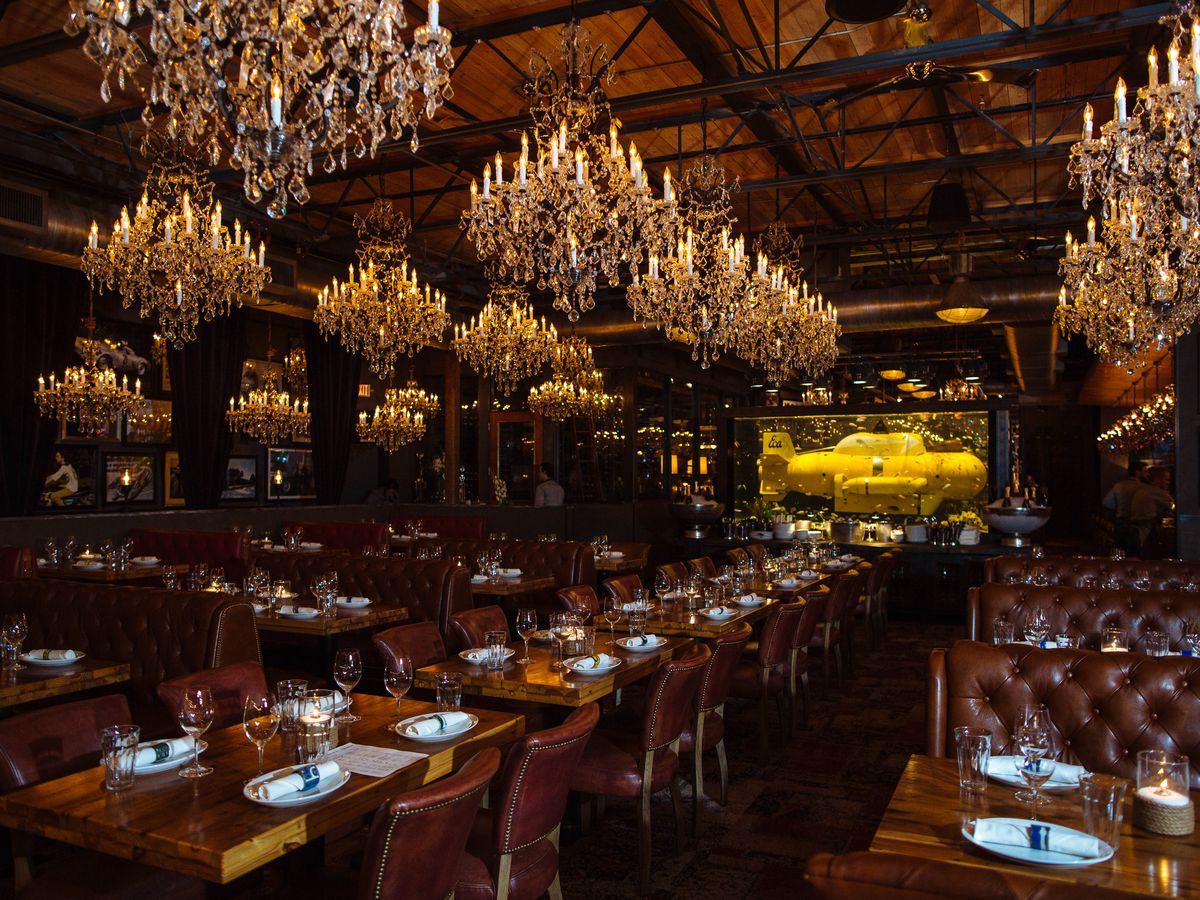A grand dining room with multiple chandeliers, tufted booths, and dim lighting