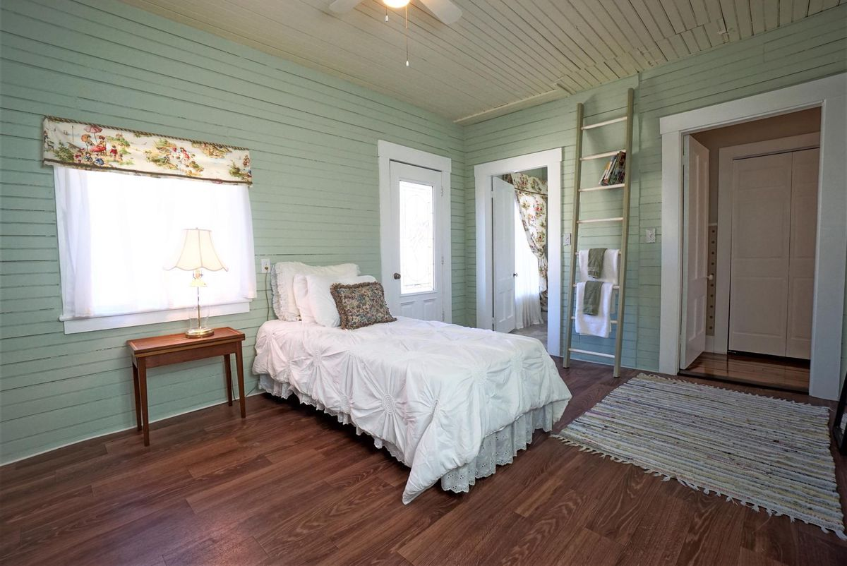 A small white bed sits on wood floors in a green room.