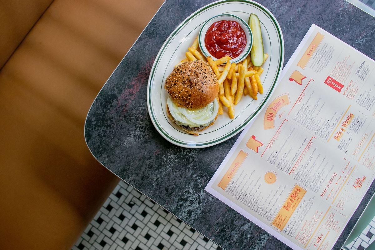 A hamburger, fries, and a pickle spear arranged on a plate with a cup of red ketchup on the side. The plate is positioned next to a restaurant menu with brown booth seating in the background.