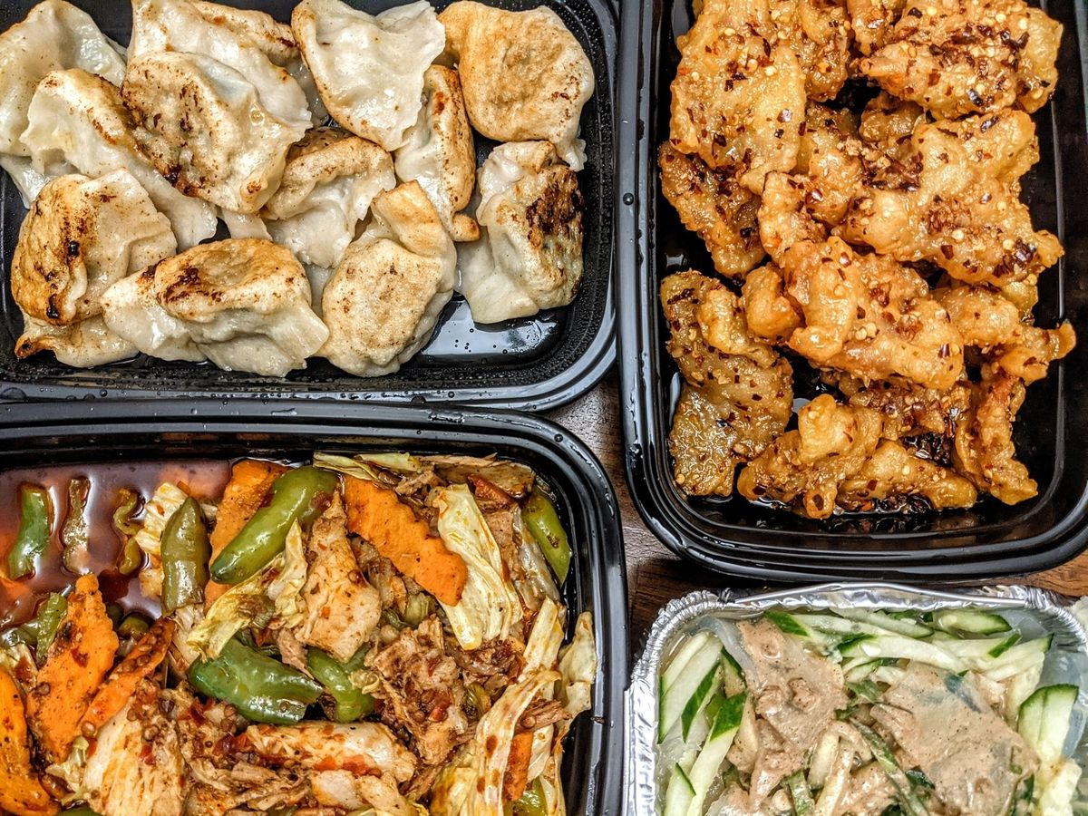 Overhead view of takeout Chinese food: Three black plastic containers hold pan-fried dumplings, crispy pork, and a sauteed pork dish with carrots. A smaller aluminum foil container has cucumbers, clear noodles, and a peanut sauce on top.
