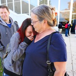 Christina Delgado holds her daughter, Isabella, as parents arrive at Mountain View High School in Orem to pick up their children after five students were stabbed in an apparent attack by a 16-year-old boy on Tuesday, Nov. 15, 2016.