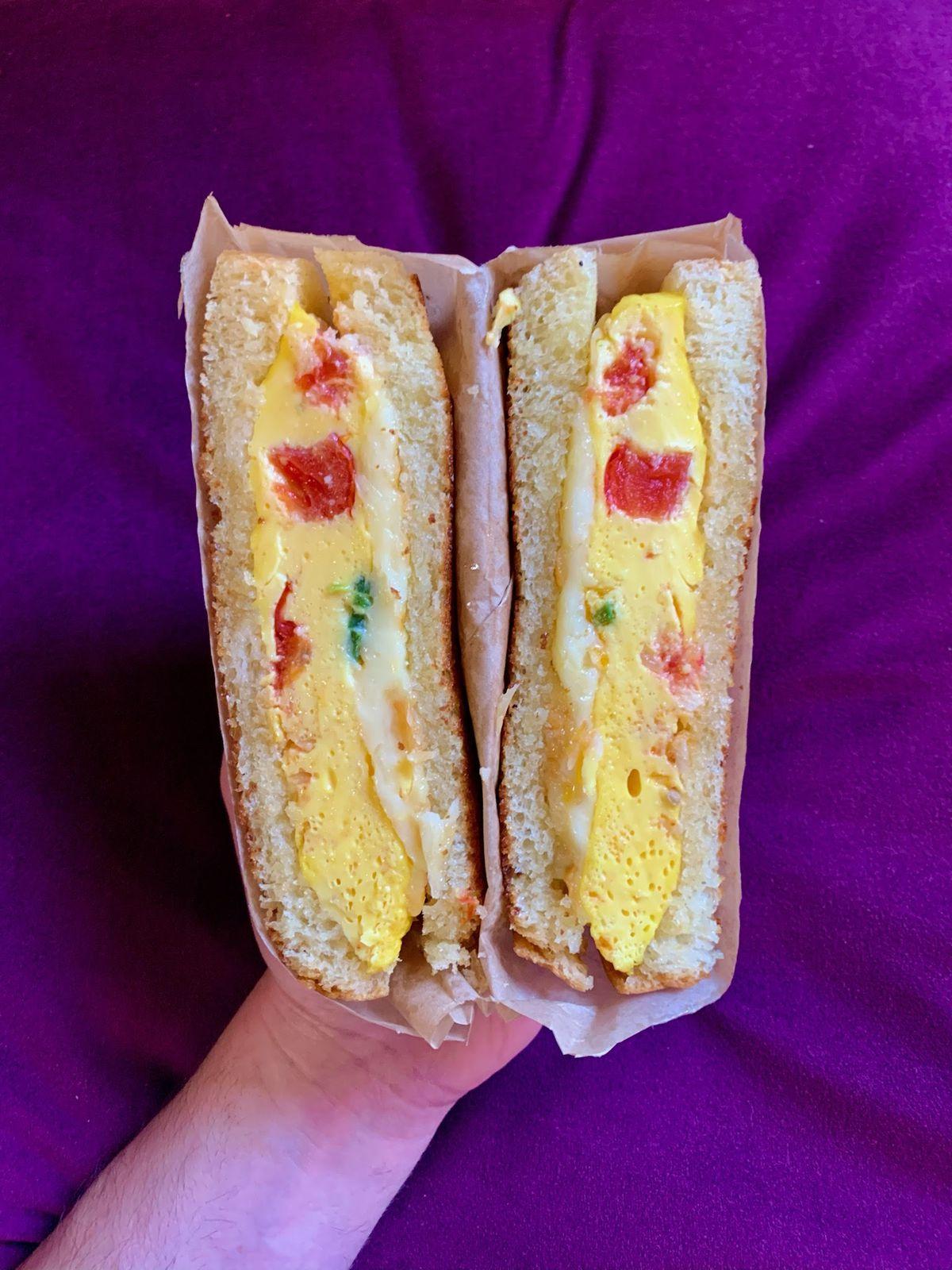 An egg breakfast sandwich held in front of a purple sheet