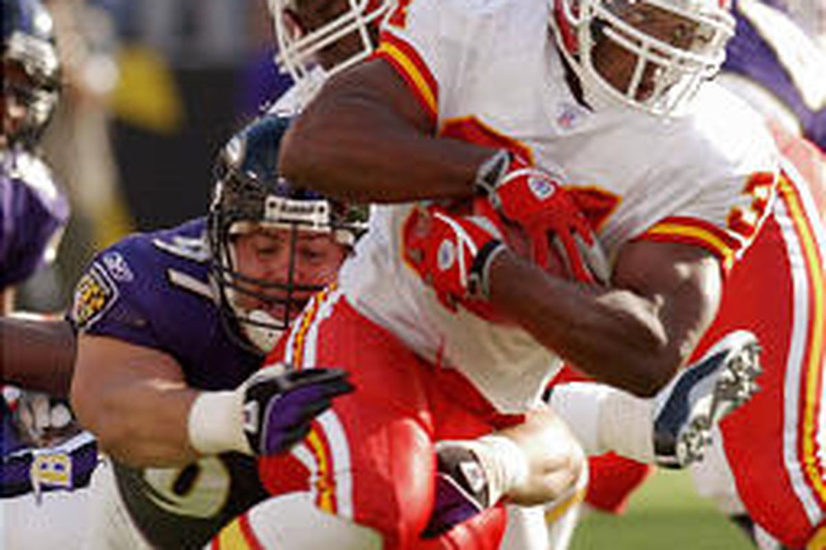 Kansas City's Priest Holmes rushes past the grasp of the Ravens' Kelly Gregg during the Chiefs' 17-10 victory Sunday in Baltimore.