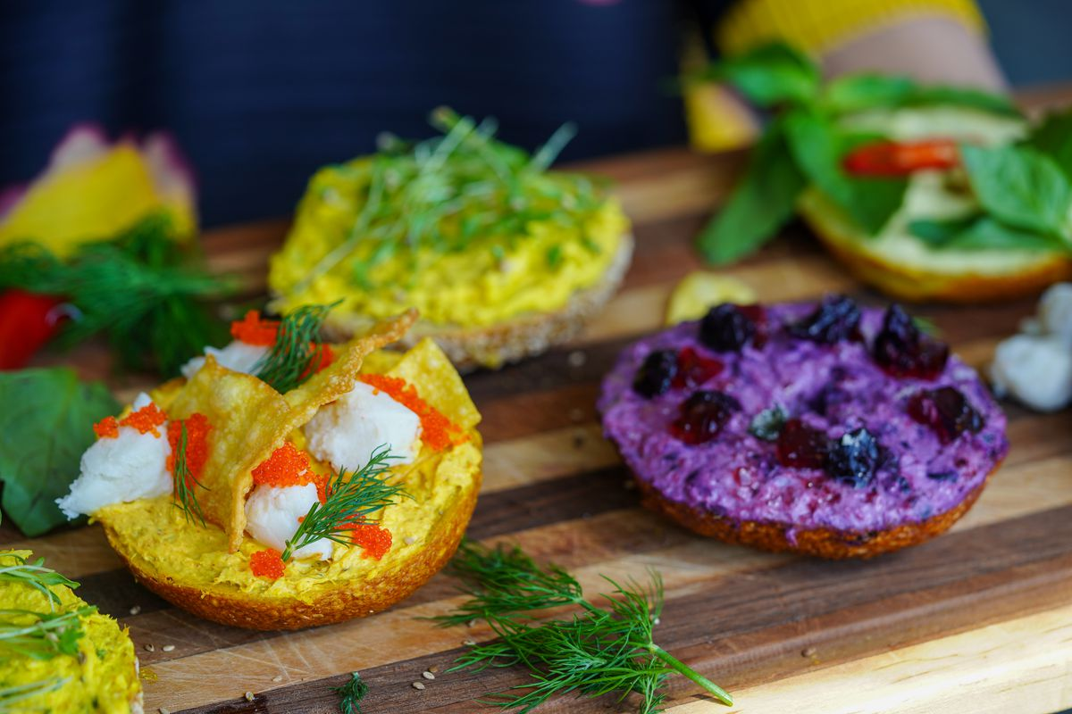 Several Bagels with Thai-inspired schmears in purple, yellow, and green with herbs