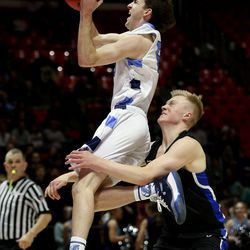 Layton's Tanner Kofoed drive to the basket and is fouled by Pleasant Grove's Preston Bushman in the 6A boys basketball quarterfinals at theHuntsman Center in Salt Lake City on Wednesday, Feb. 26, 2020.
