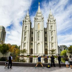 People gather by the Temple Square reflecting pool during the morning session of the 185th Semiannual General Conference of The Church of Jesus Christ of Latter-Day Saints in Salt Lake City on Sunday, Oct. 4, 2015.
