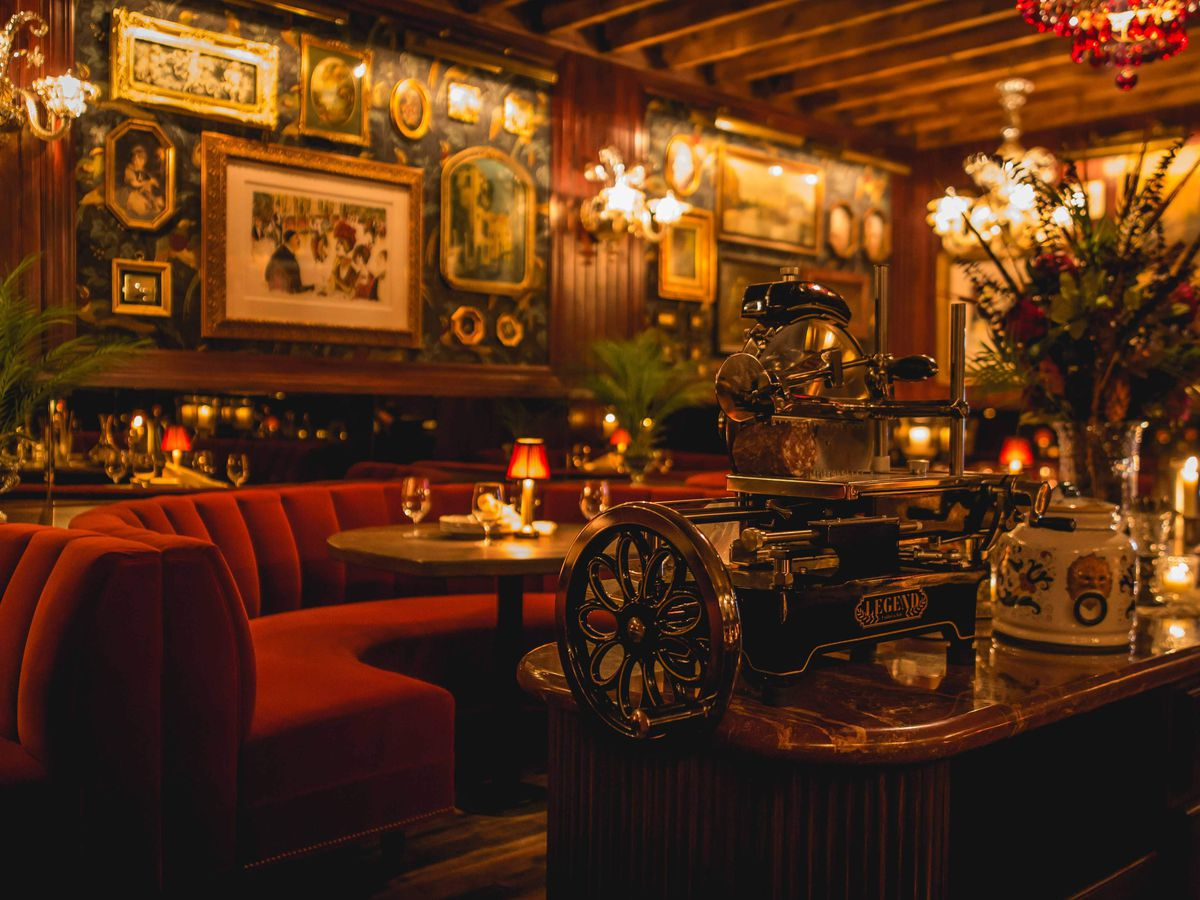 The dimly-lit dining room of a new Italian restaurant with red booths, vintage framed photographs, and chandeliers.
