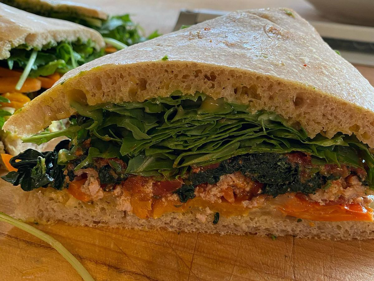 Meatball sandwich at Standard Fare, loaded with sautéed onions, marinated sweet peppers, garlicky kale, marjoram aïoli, and a large amount of arugula