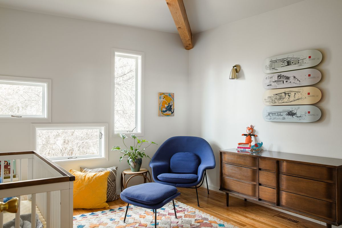 A nursery with a blue armchair, wooden dresser, white crib, and patterned area rug. There are multiple windows and artwork also hangs above the dresser.