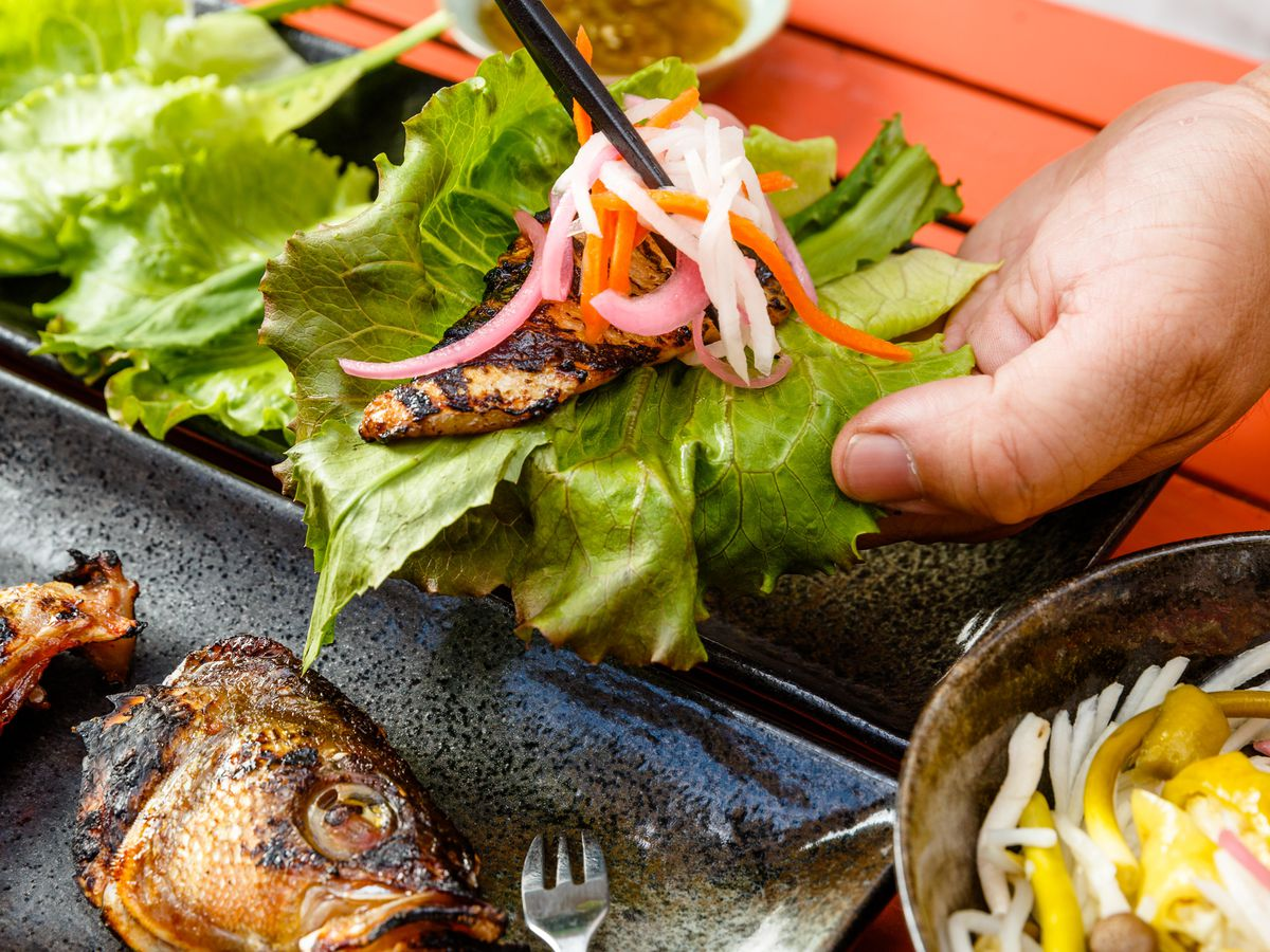 A patron adds slaw to a fish belly lettuce wrap.