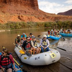Sen. Mitt Romney, R-Utah, center left, his wife, Ann, and state Sen. David Hinkins, R-Orangeville, sit together in a raft as a large group floats down a section of the Colorado River northeast of Moab on Saturday, Sept. 18, 2021.