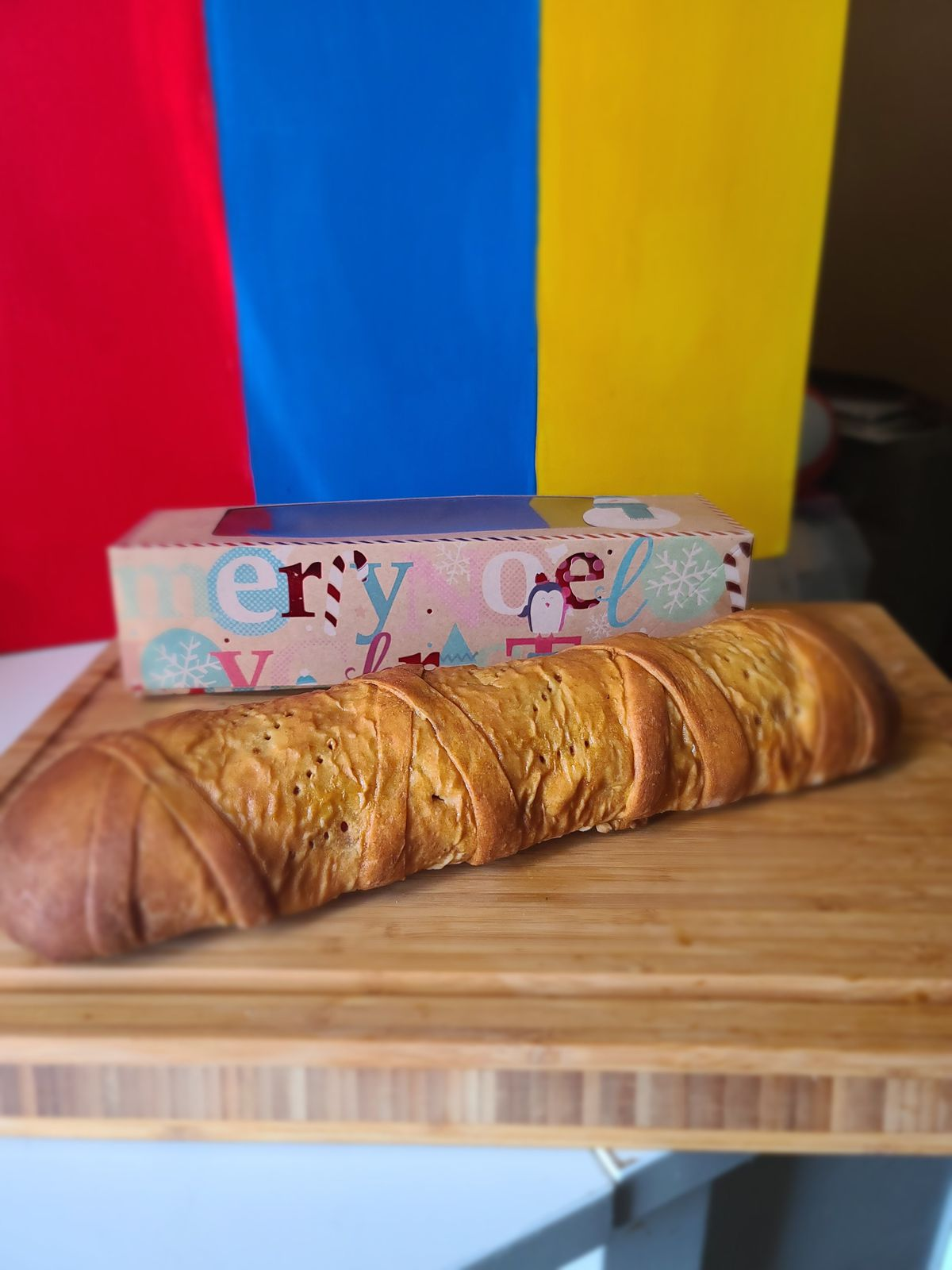 Pan de jamon, a traditional Venezuelan Christmas bread, on a table in front of a wrapped present