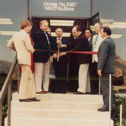 Larry H. Miller, left, cuts the ribbon during the grand opening for the new location of the Murray Toyota dealership in 1983.