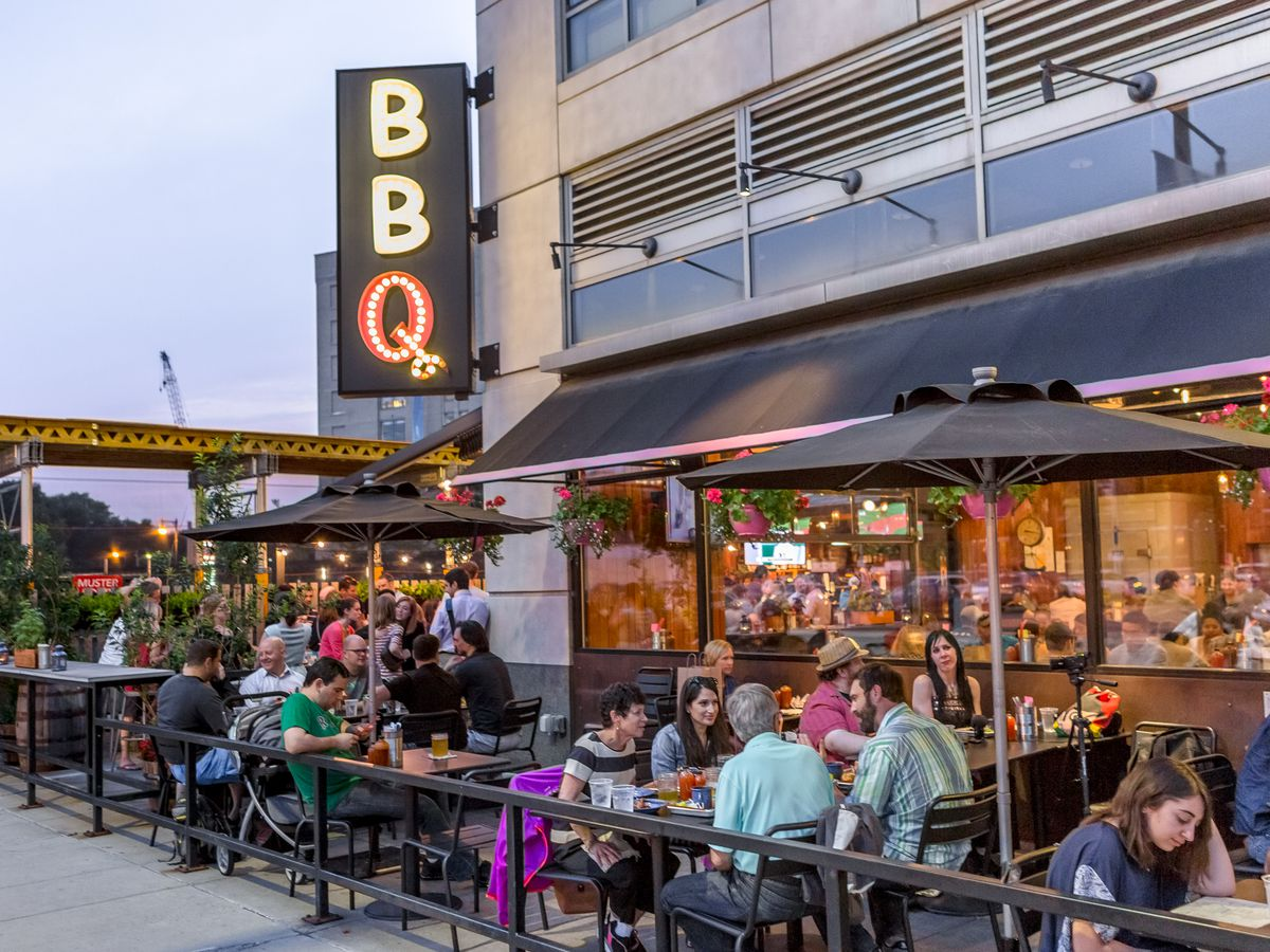 """A sidewalk patio full of patrons outside of a restaurant with """"BBQ"""" signage"""