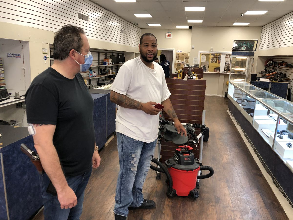 Pawnbroker Scott Lee Cohen, left, and his employee Robert Ross recount the May 31 break-in at the pawn shop at 90th and Commercial.