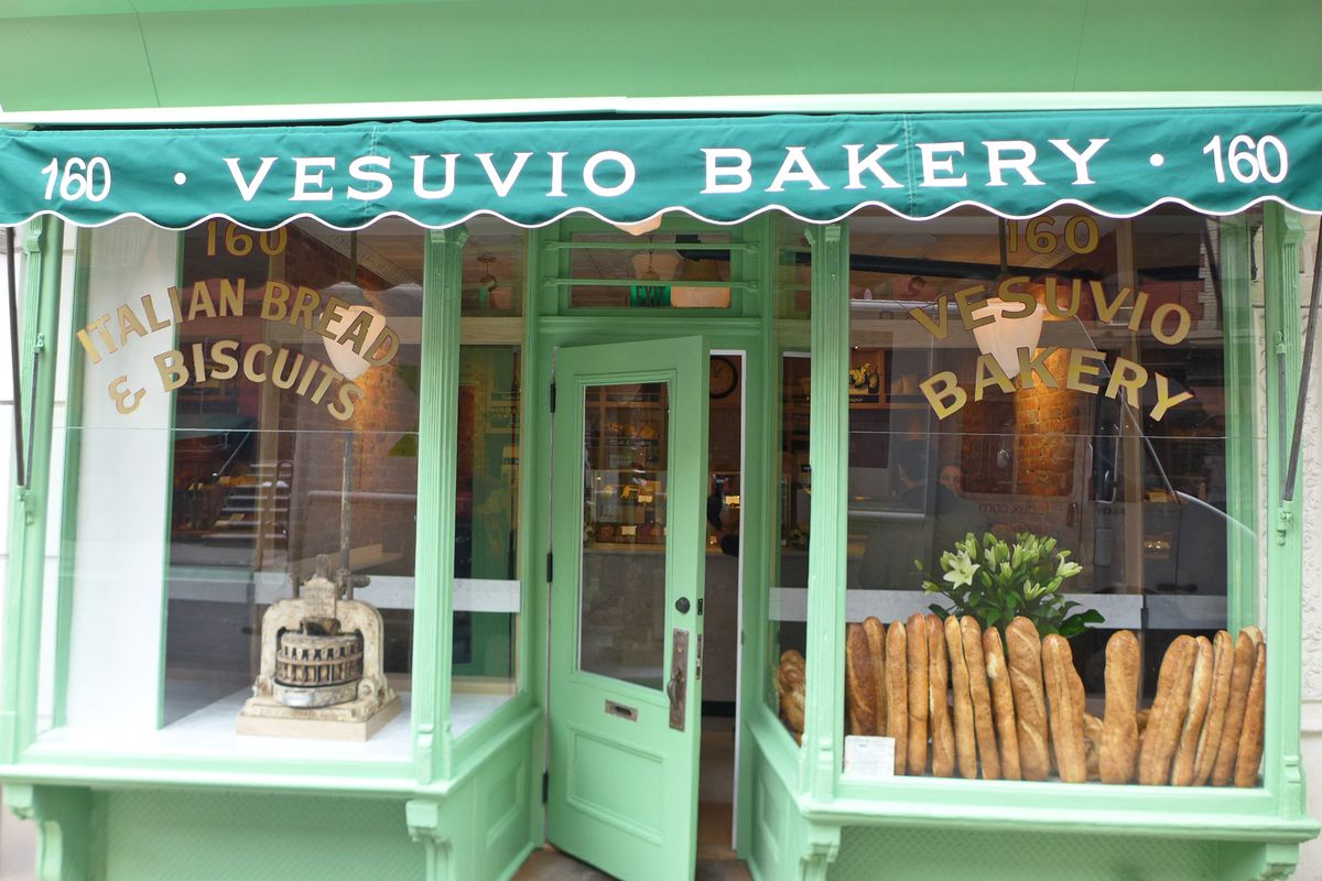A green fronted bakery with long loaves in the window.
