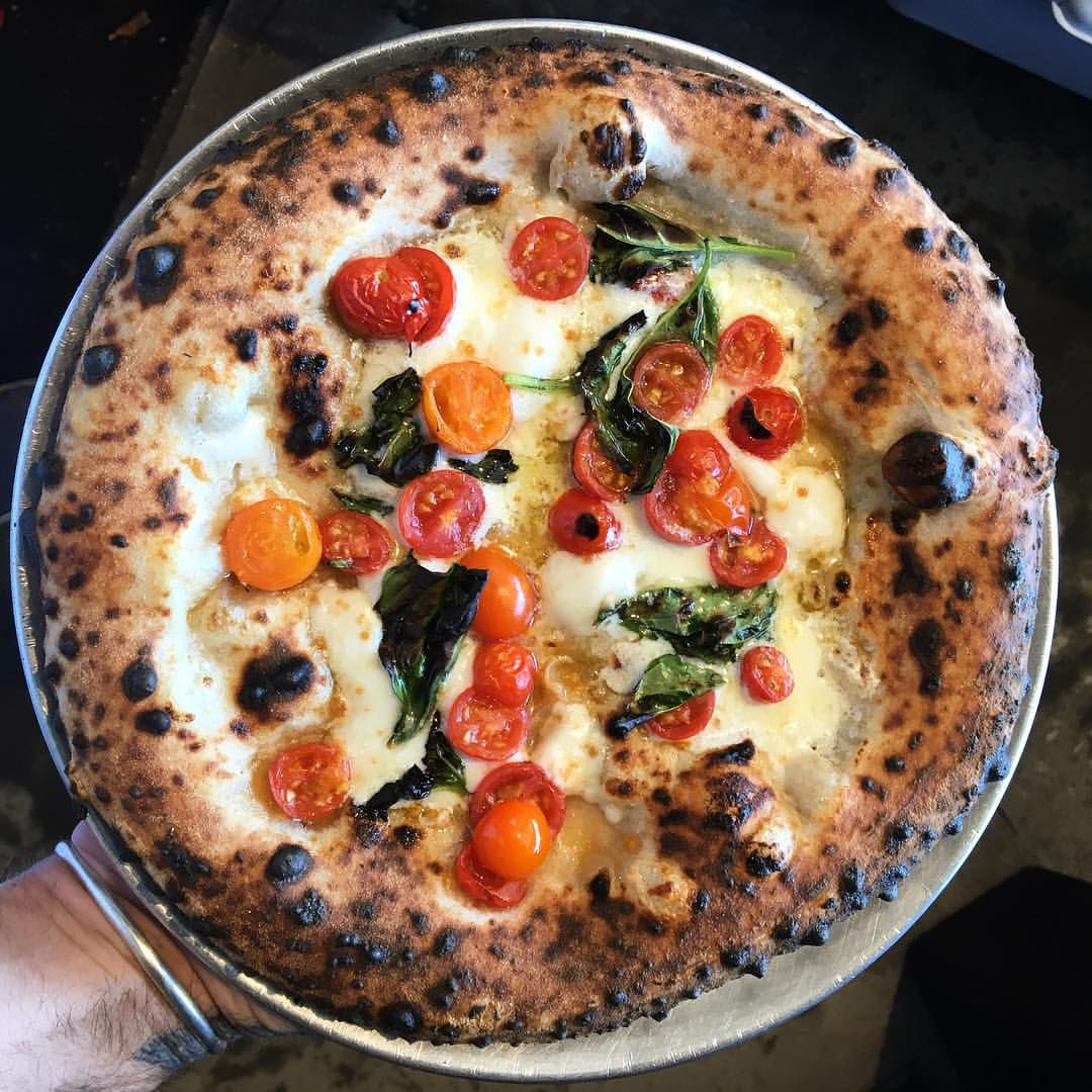Pizza with spotted crust, tomatoes, and cheese