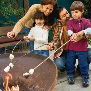 Family Roasting Marshmallows Over Backyard Fire Pit