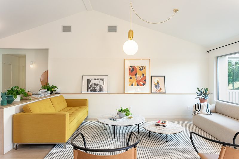 Living area with a yellow couch, two round coffee tables, and a large pendant lamp.
