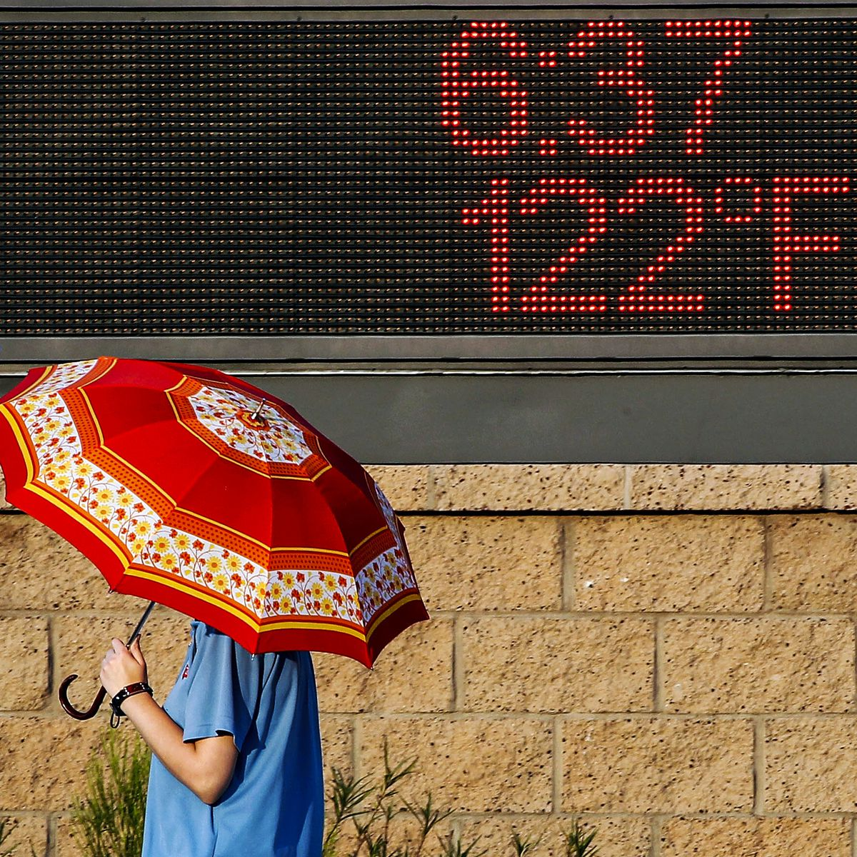 A pedestrian uses an umbrella to get some relief from the sun as she walks past a sign displaying the temperature on June 20, 2017 in Phoenix, Arizona.
