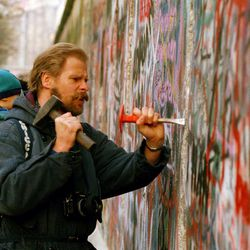 A sight-seeing West Berliner carries his baby and uses a hammer and chisel to carve out a piece of the Berlin Wall, Nov. 14, 1989. Many souvenir hunters come to the Berlin to break pieces off the crumbling wall.