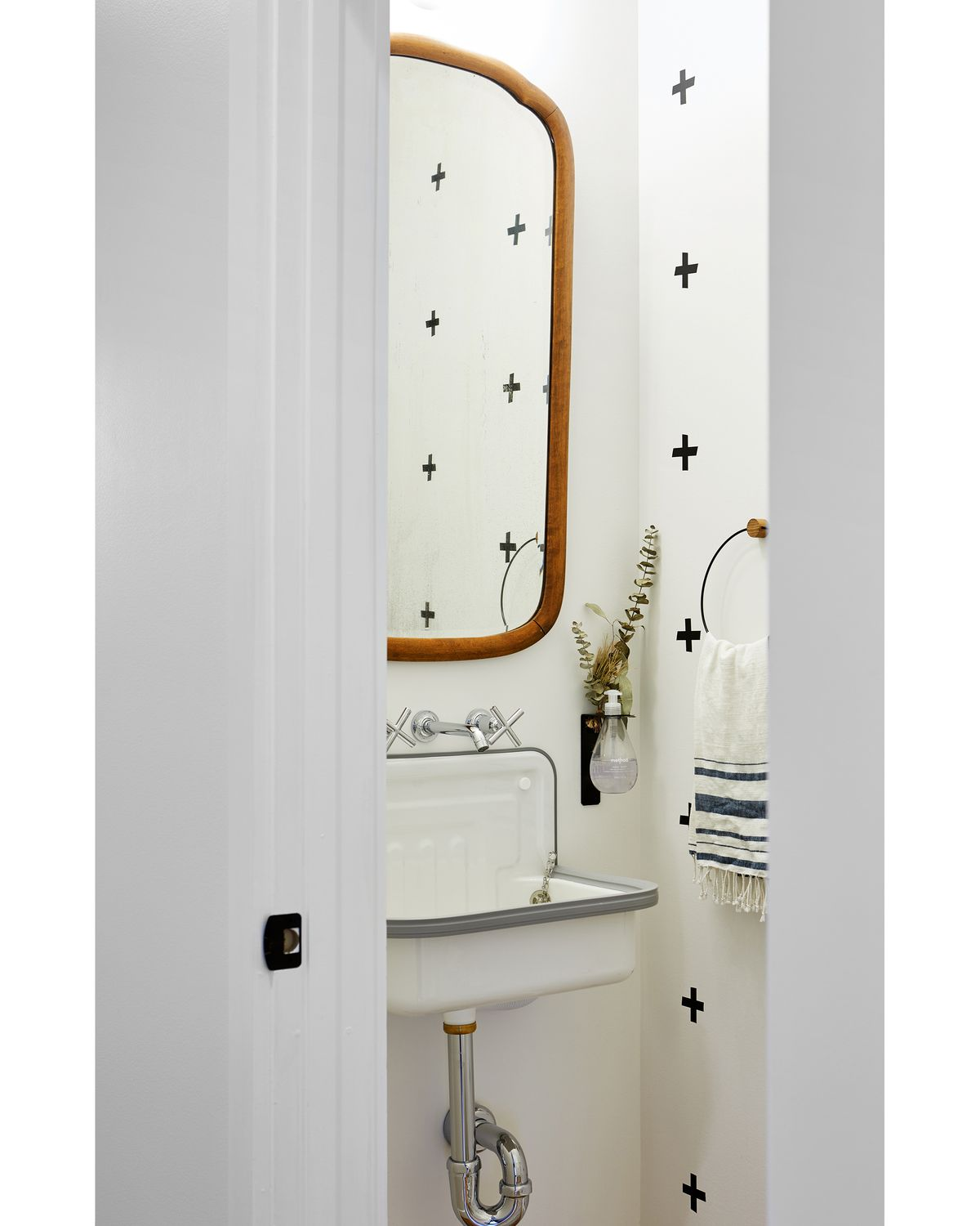 A bathroom. The wall is white with a black cross pattern. There is a wooden mirror, a sink, and a towel holder holding a blue and white patterned hand towel.