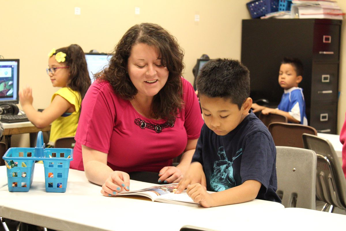 Ana Gramajo, left, is the co-director of HOPE Online Action Academy in Aurora. Here she works with a student on reading.