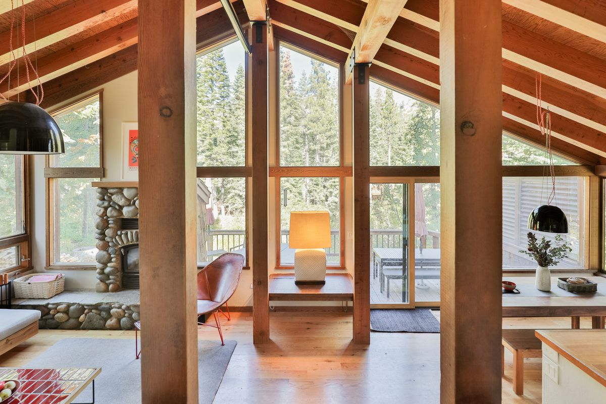 A wood framed room with exposed beams and a vaulted ceilings. Trees are be seen via the windows.