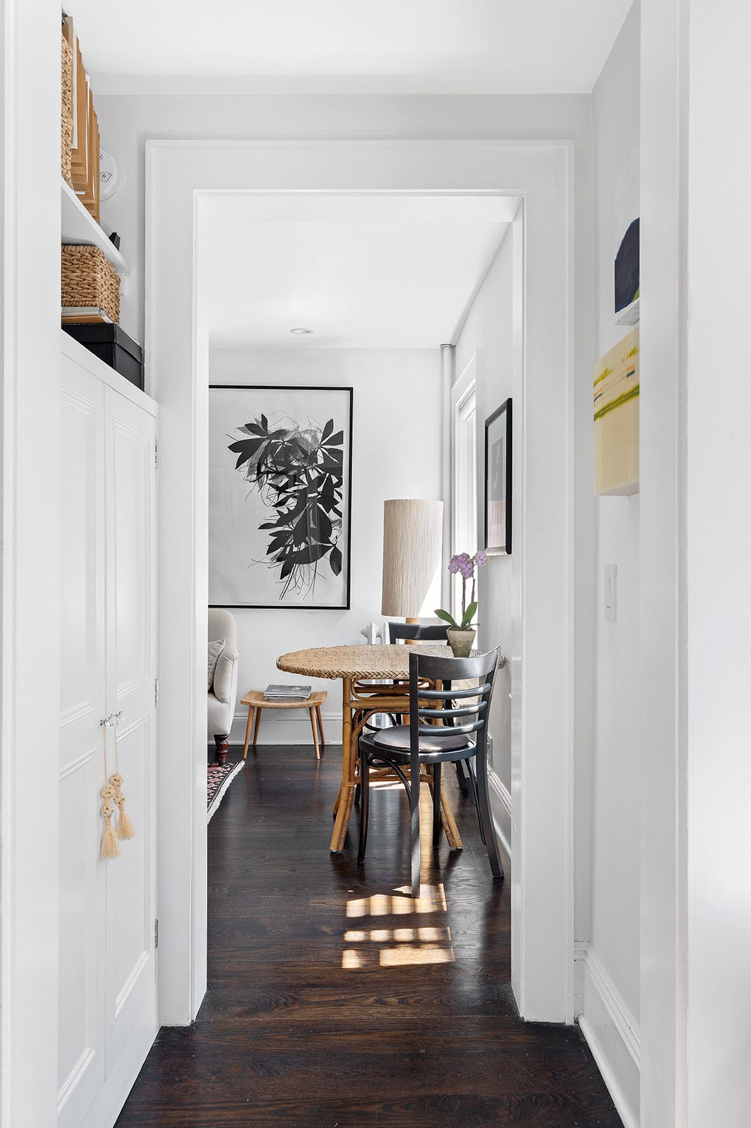 A hallway with hardwood floors, base moldings, and white cabinets.