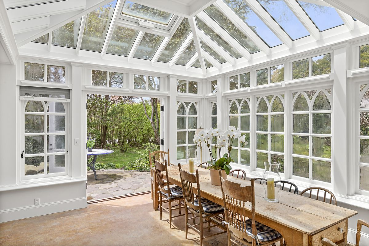 An enclosed dining area with a wood table and white trimmed windows and skylights.