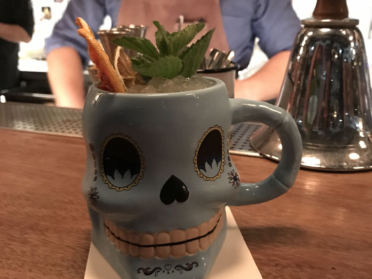 A cocktail on the bar in a decorative, goofy skull mug, with a cinnamon stick, herbal garnish and crushed ice sticking out above the rim.