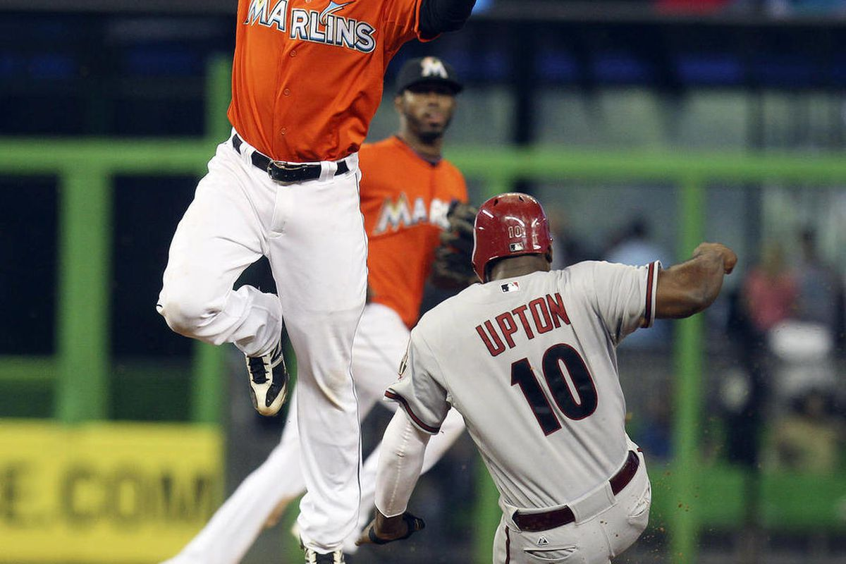Miami Marlins second baseman Omar Infante is unable to make a play as Arizona Diamondbacks runner Justin Upton slides safely into second  during the eighth inning of the baseball game in Miami, Monday, April 302, 2012. The Diamondbacks won 9-5.